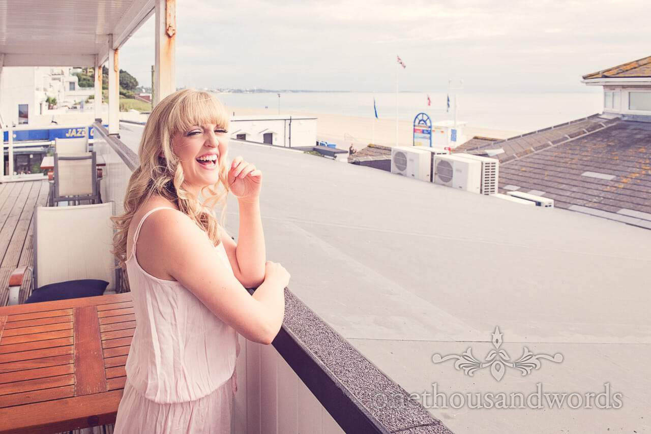 Blonde bride laughs on balcony overlooking the sea at Sandbanks Hotel wedding