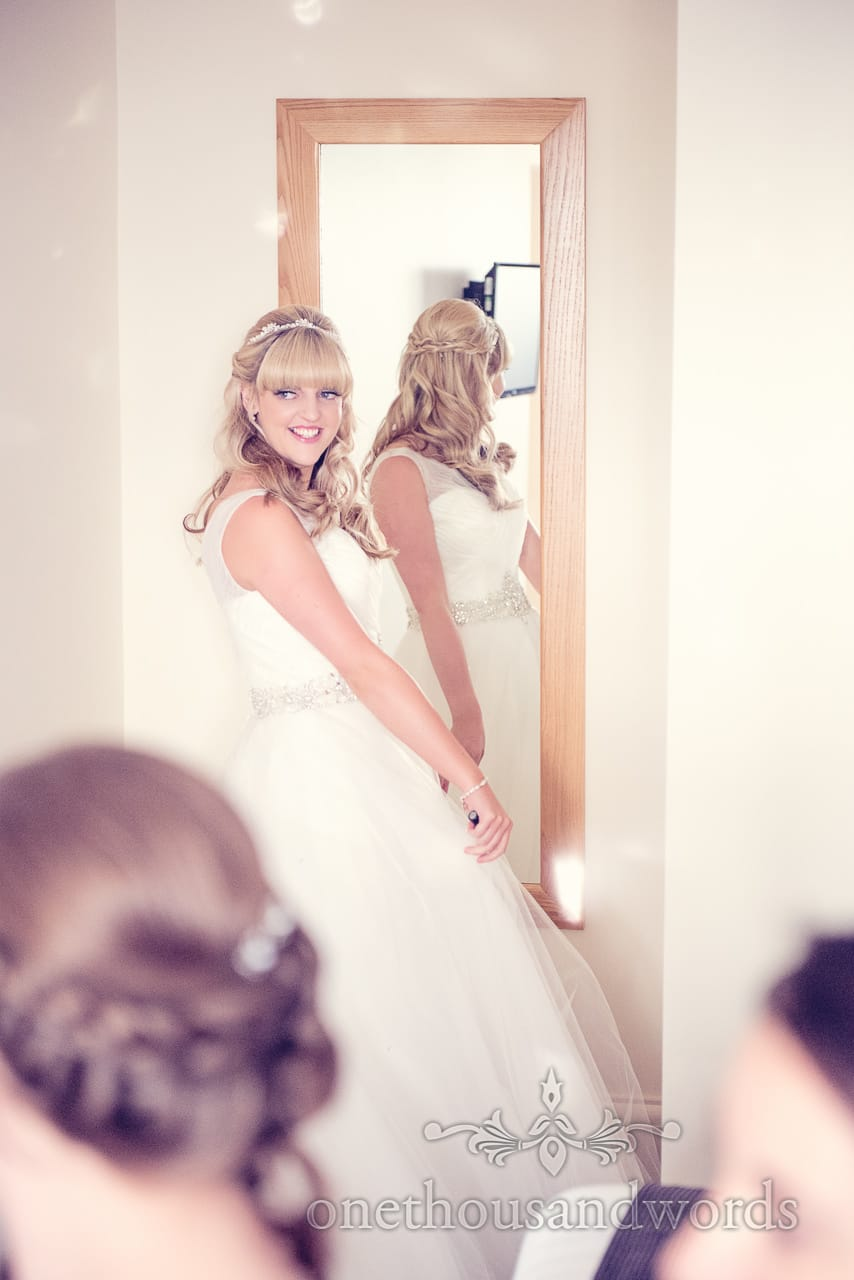 Blonde bride looks back from mirror on wedding morning at Sandbanks Hotel wedding