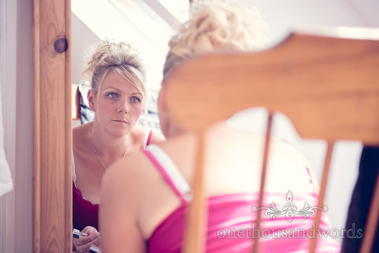 Blonde bride with bright blue eyes looks at her wedding makeup in a mirror