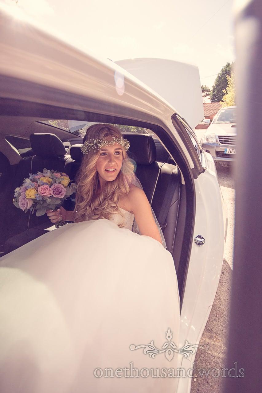 Blonde bride with floral head dress and pastel wedding boquet in Jaguar wedding car