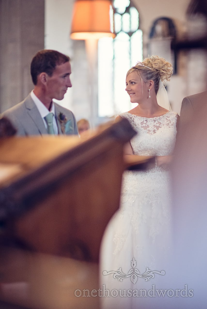 Blonde bride with pearl earrings looks at her groom during Swanage church wedding