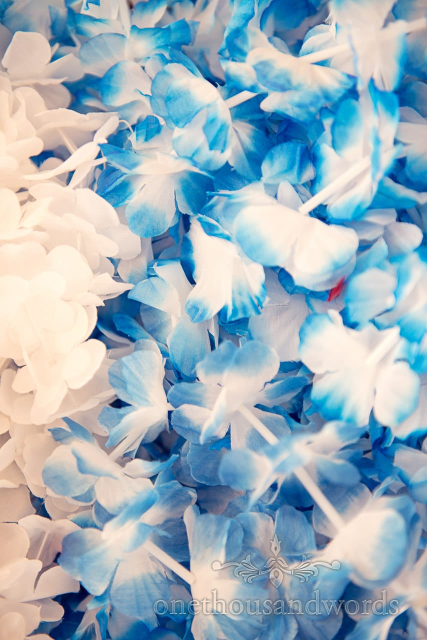 Blue and white hawaiian leis for seaside theme wedding in Dorset