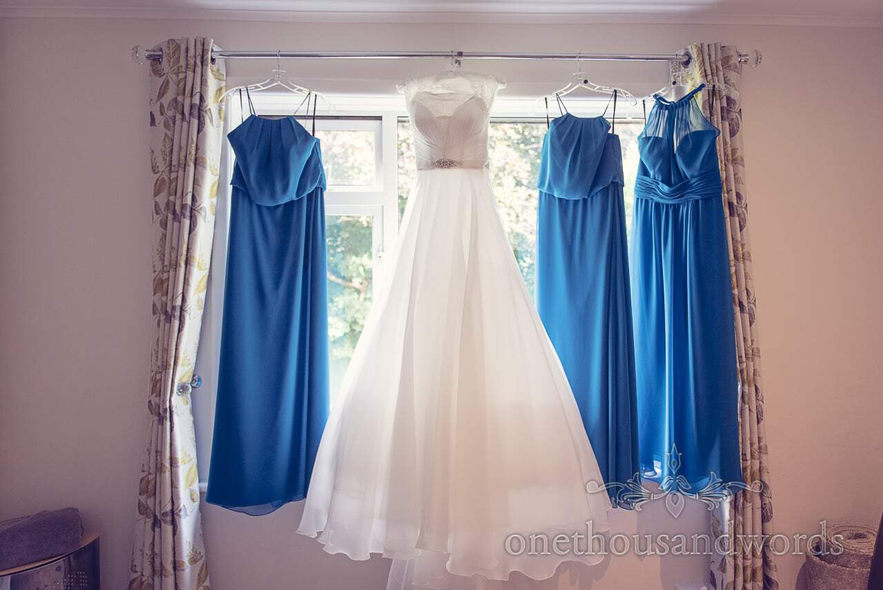 Blue bridesmaids dresses hang with white wedding dress in window