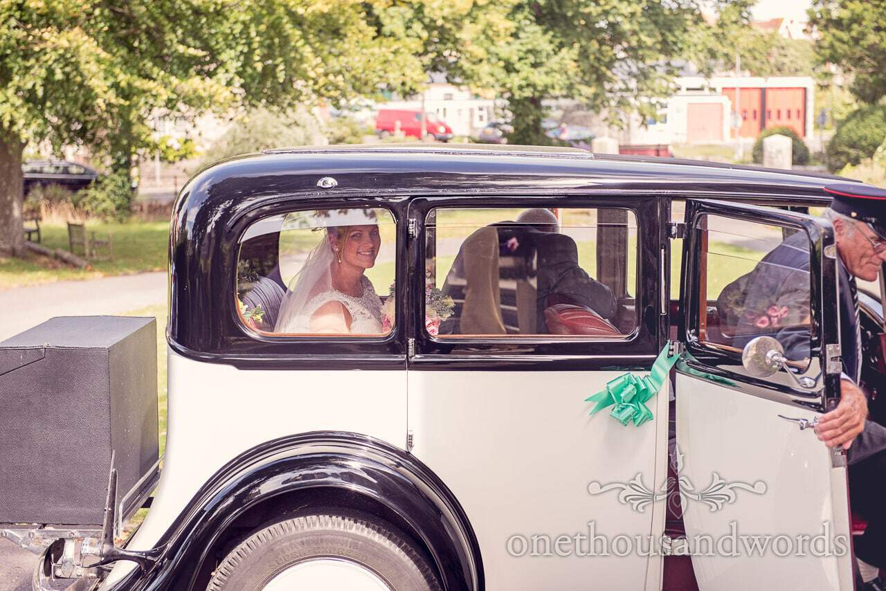 Brde in classic wedding car arrives at Swanage Church wedding ceremony