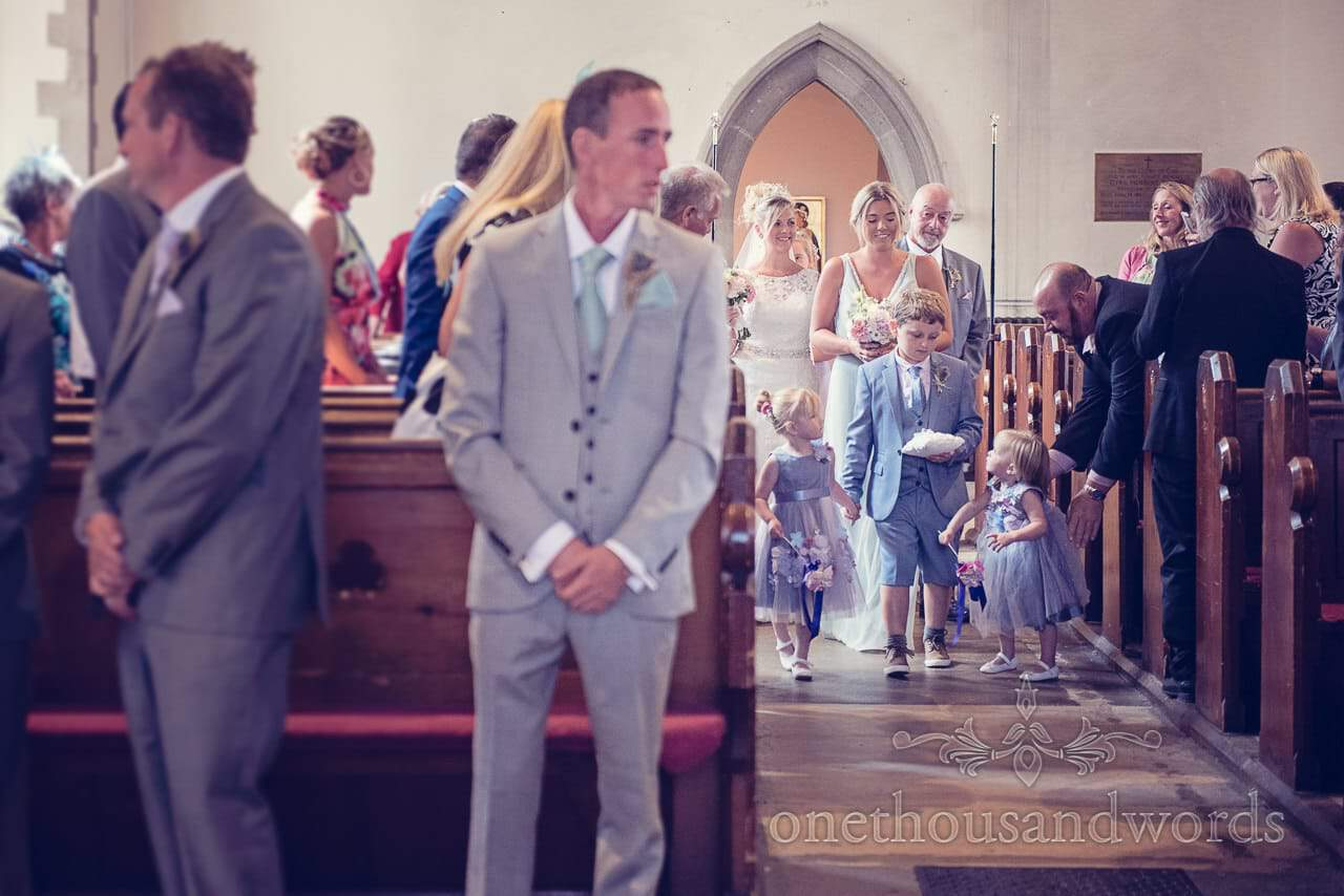 Bridal party enters Swanage church weddign ceremony as groom waits