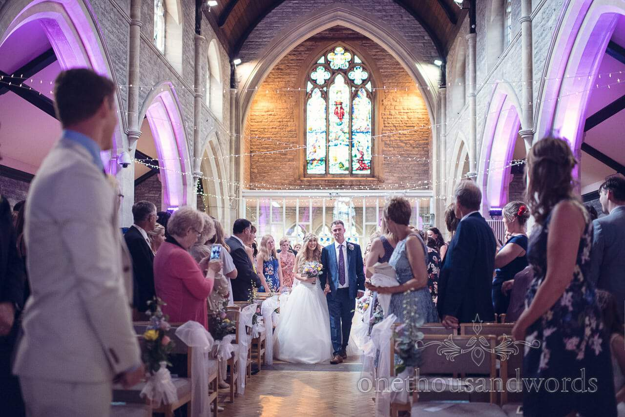 Bride and father walk down the aisle in church lit with purple lights at Poole wedding