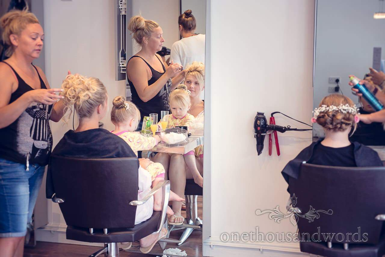 Bride and flower girl have wedding hair styled at hairdressers on wedding morning