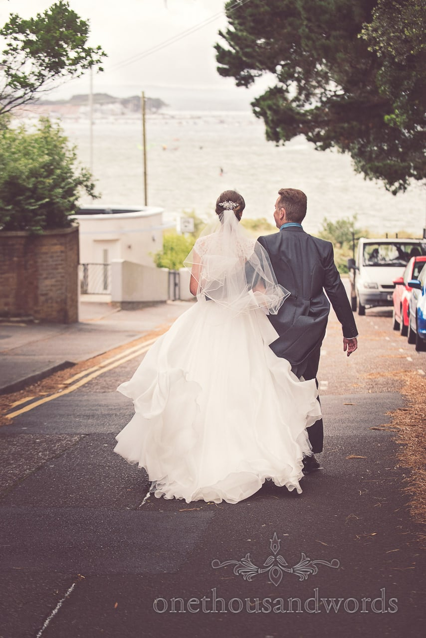 Bride and grom walk down towards the sea at Harbour Heights wedding