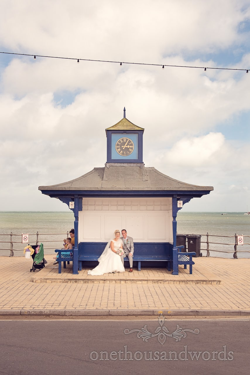 Bride and groom by the sea in Swanage clock tower wooden hut bench