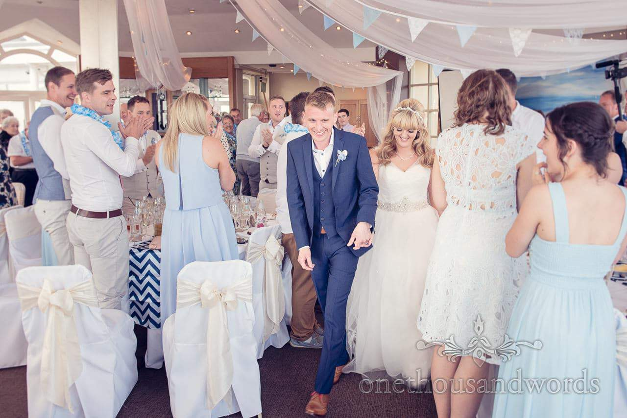 Bride and groom enter seaside theme wedding breakfast at Sandbanks Hotel