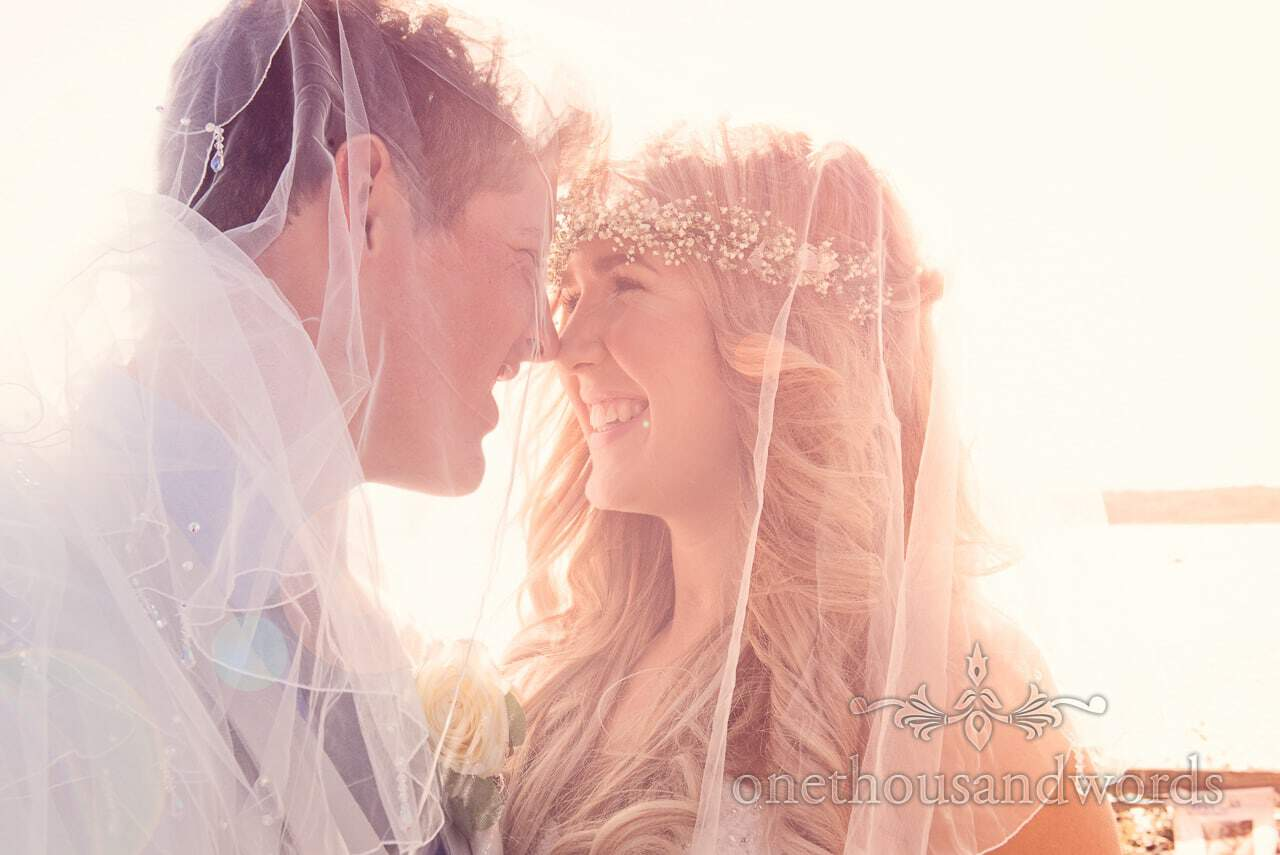 Bride and groom eskimo kiss under wedding veil with soft sunshine