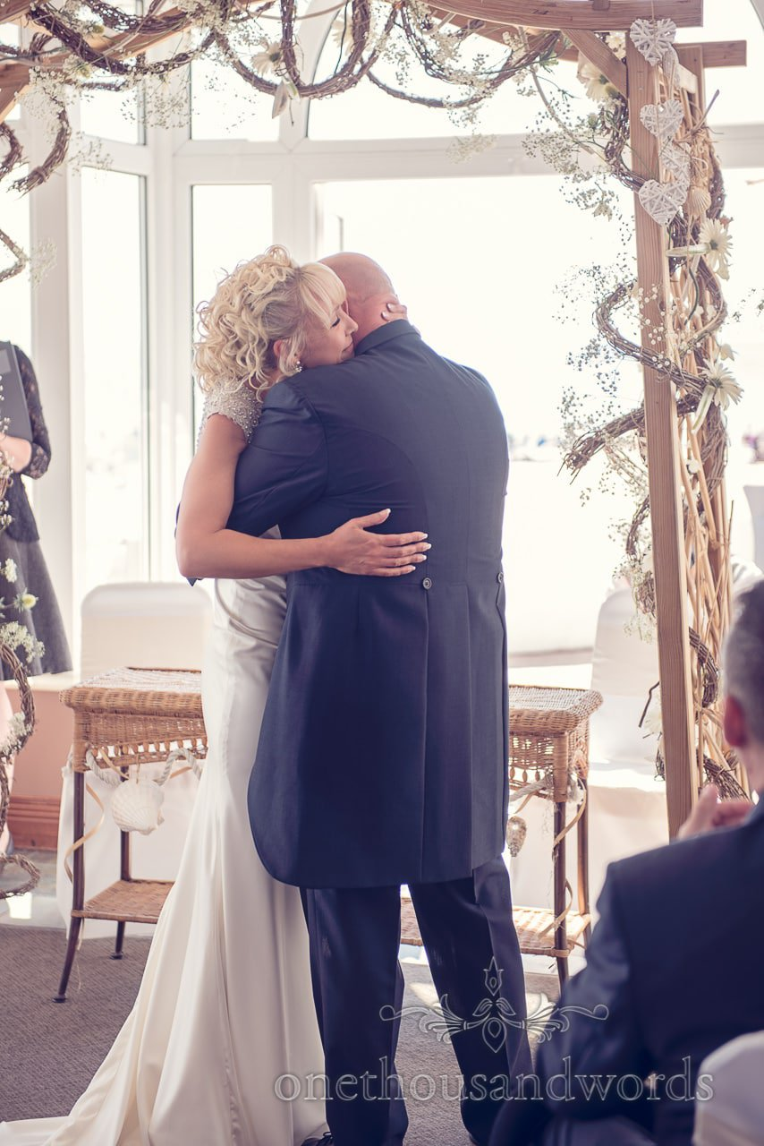 Bride and groom hug during wedding ceremony at Sandbanks Hotel Wedding venue