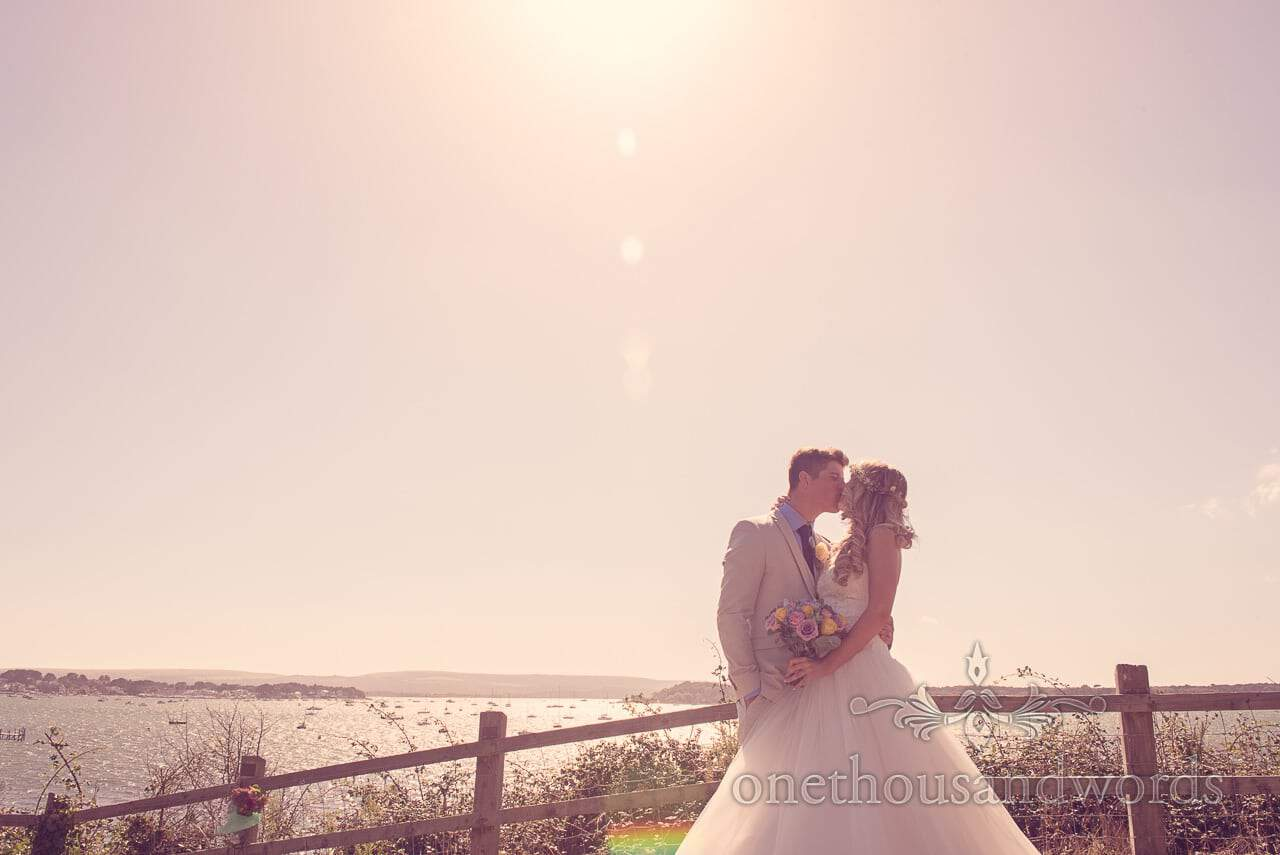Bride and groom kiss at Evening Hill overlooking Poole Harbour in Dorset