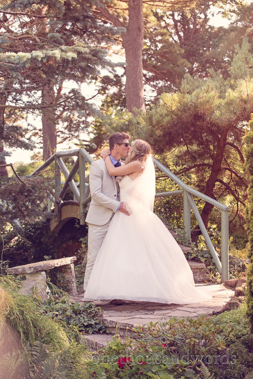 Bride and groom kiss in Compton Acres gardens at italian villa wedding photographs