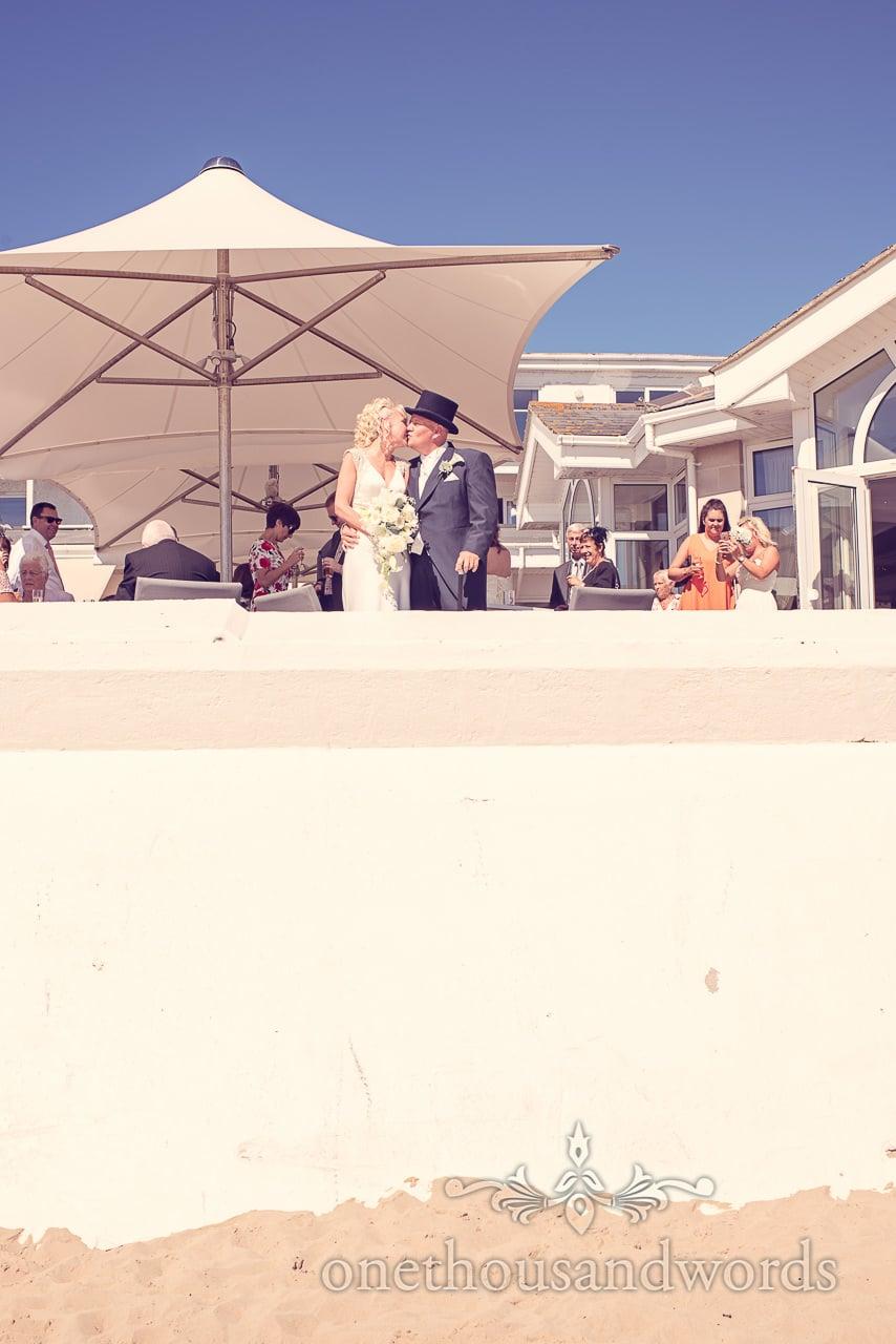 Bride and groom kiss overlooking the beach at Sandbanks Hotel Wedding reception