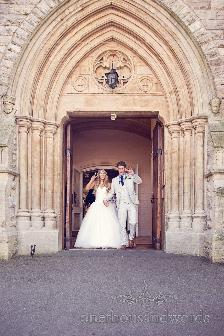 Bride and groom leave St Marys Longfleet church under stone archway rock and peace signs