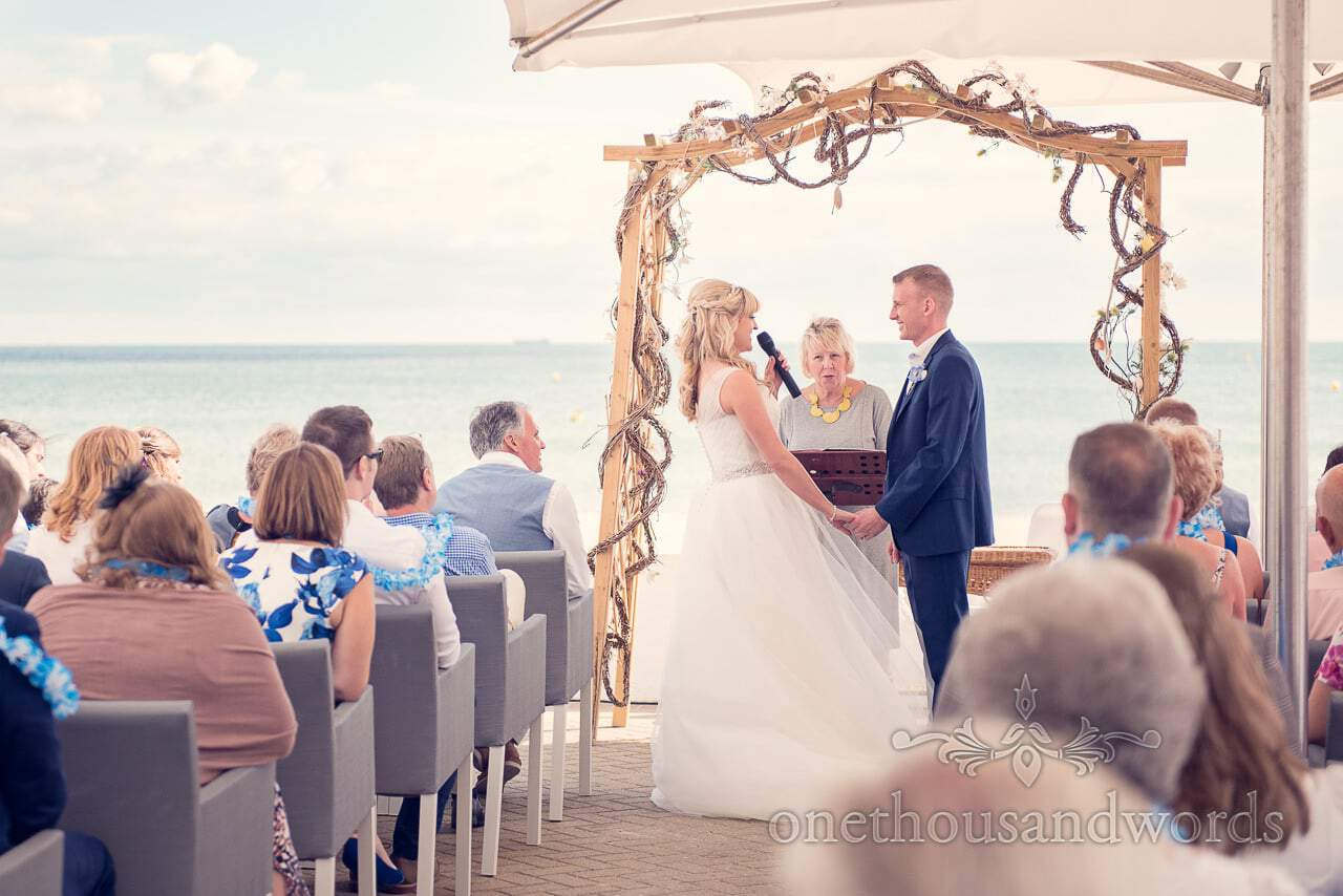 Bride and groom make their vows by the sea at outdoor wedding ceremony
