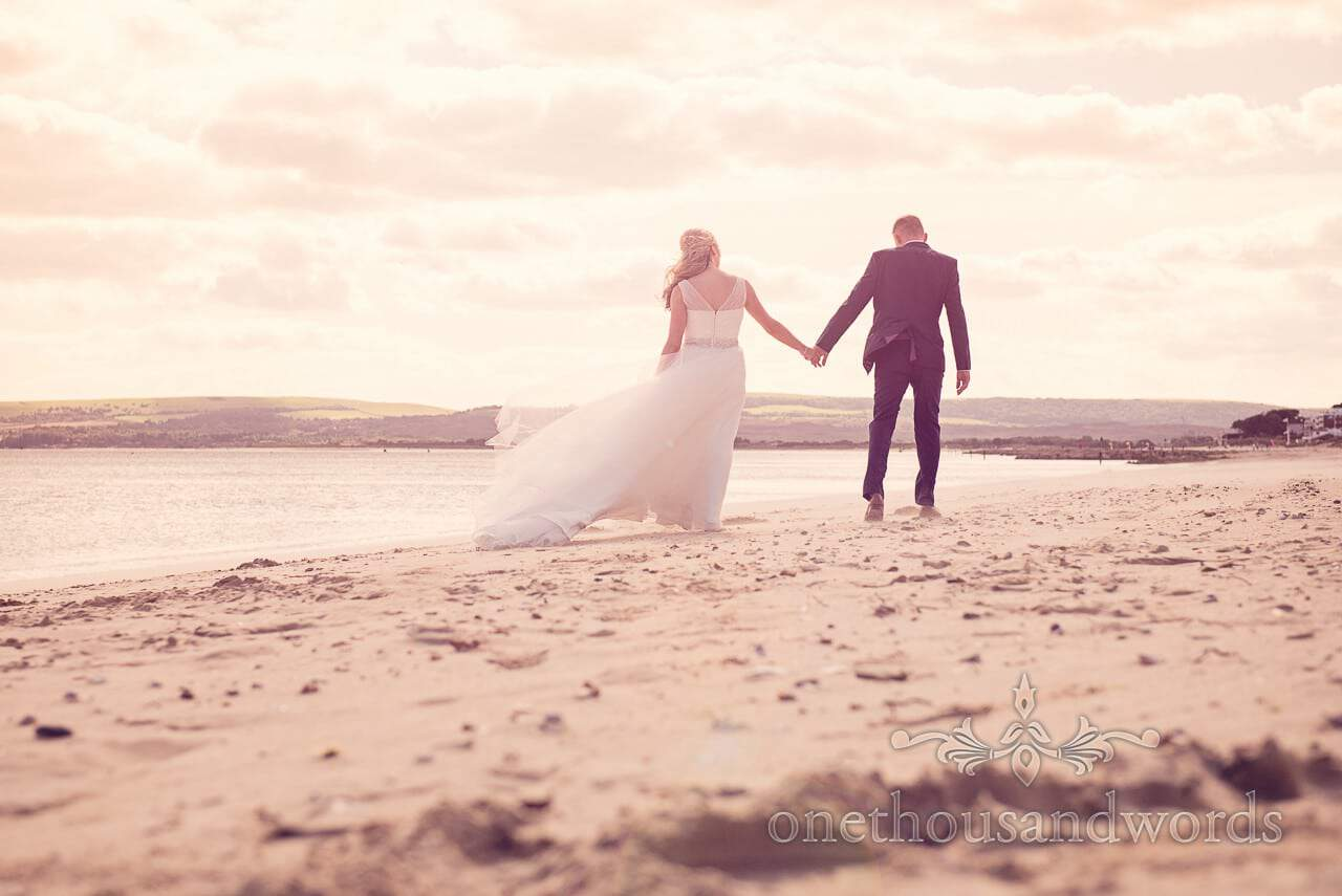Bride and groom on Dorset beach for sunset at seaside theme wedding photographs