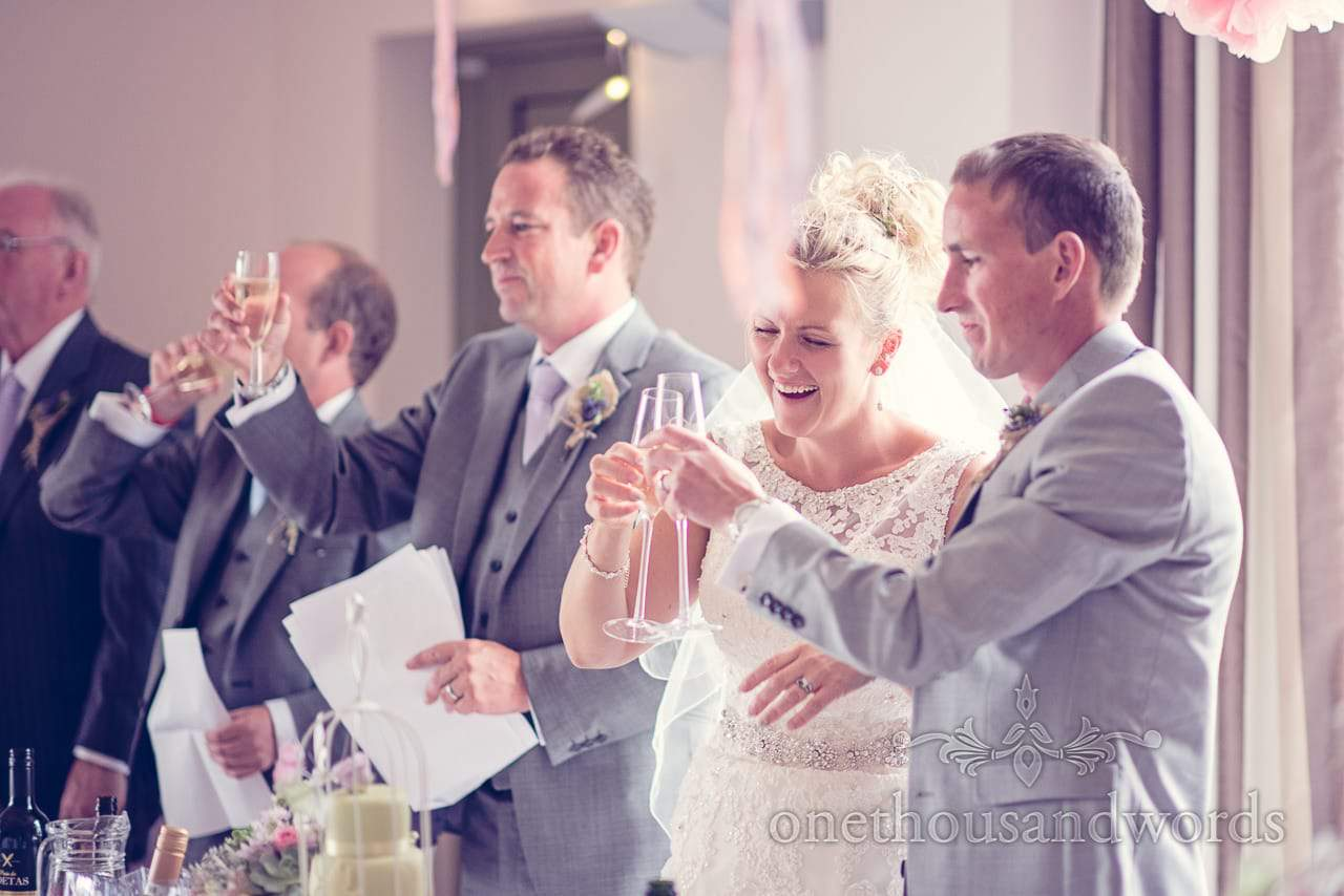 Bride and groom raise champagne glasses at Harmans Cross Village Hall Wedding