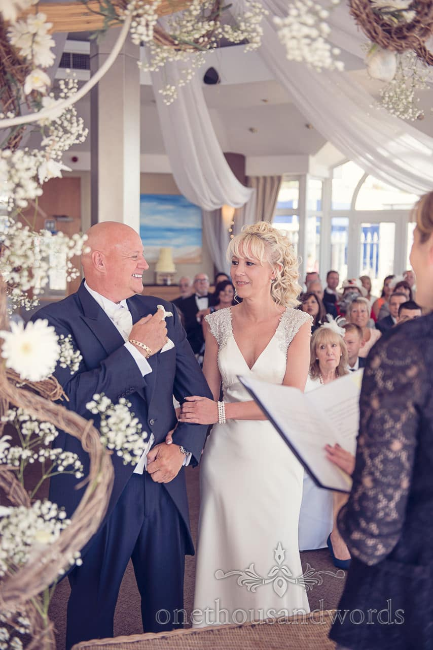 Bride and groom under flower arbour at Sandbanks Hotel Wedding ceremony
