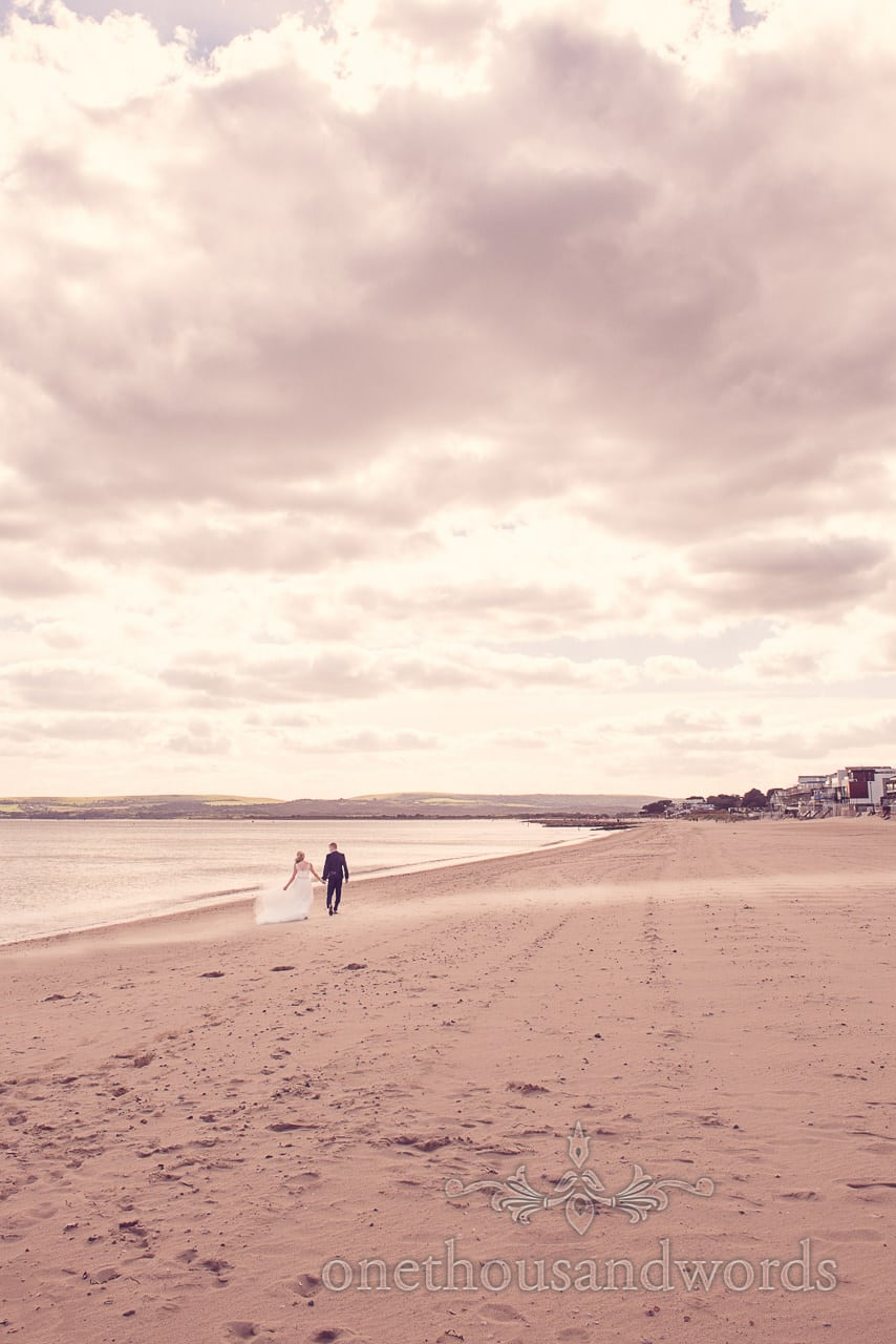 Bride and groom walk along Sandbanks beach at seaside theme wedding photographs
