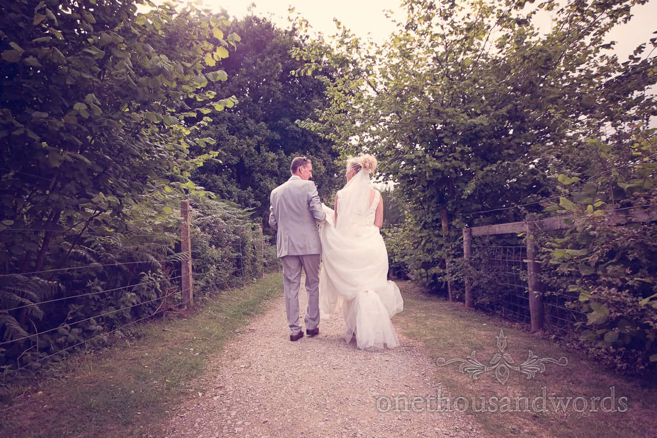 Bride and groom walk down countryside path together at Harmans Cross Wedding