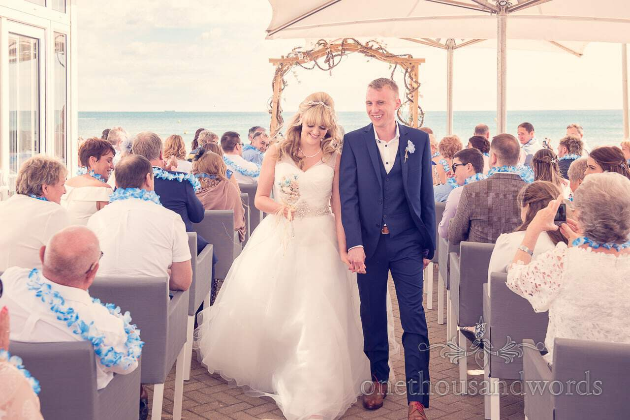 Bride and groom walk down the aisle at outdoor wedding ceremony by the sea