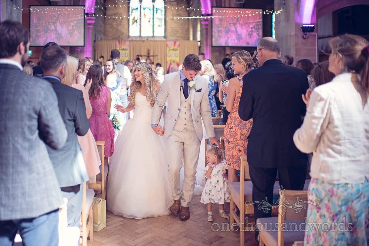 Bride and groom walk down the aisle at St Marys Longfleet church wedding with fairy lights