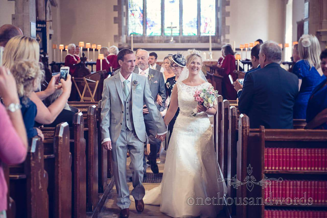 Bride and groom walk down the aisle in Swanage church wedding