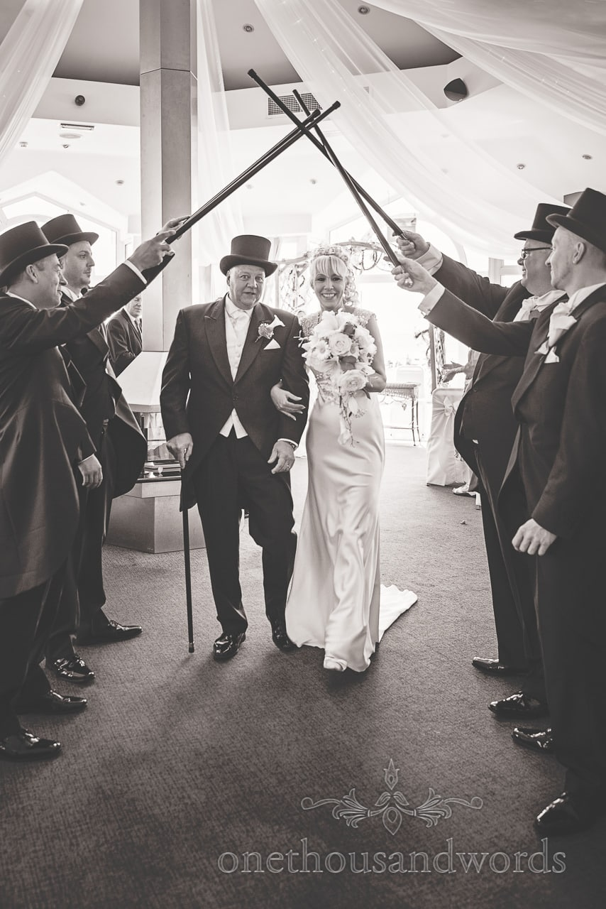 Bride and groom walk under guard of honour with canes at Sandbanks Hotel