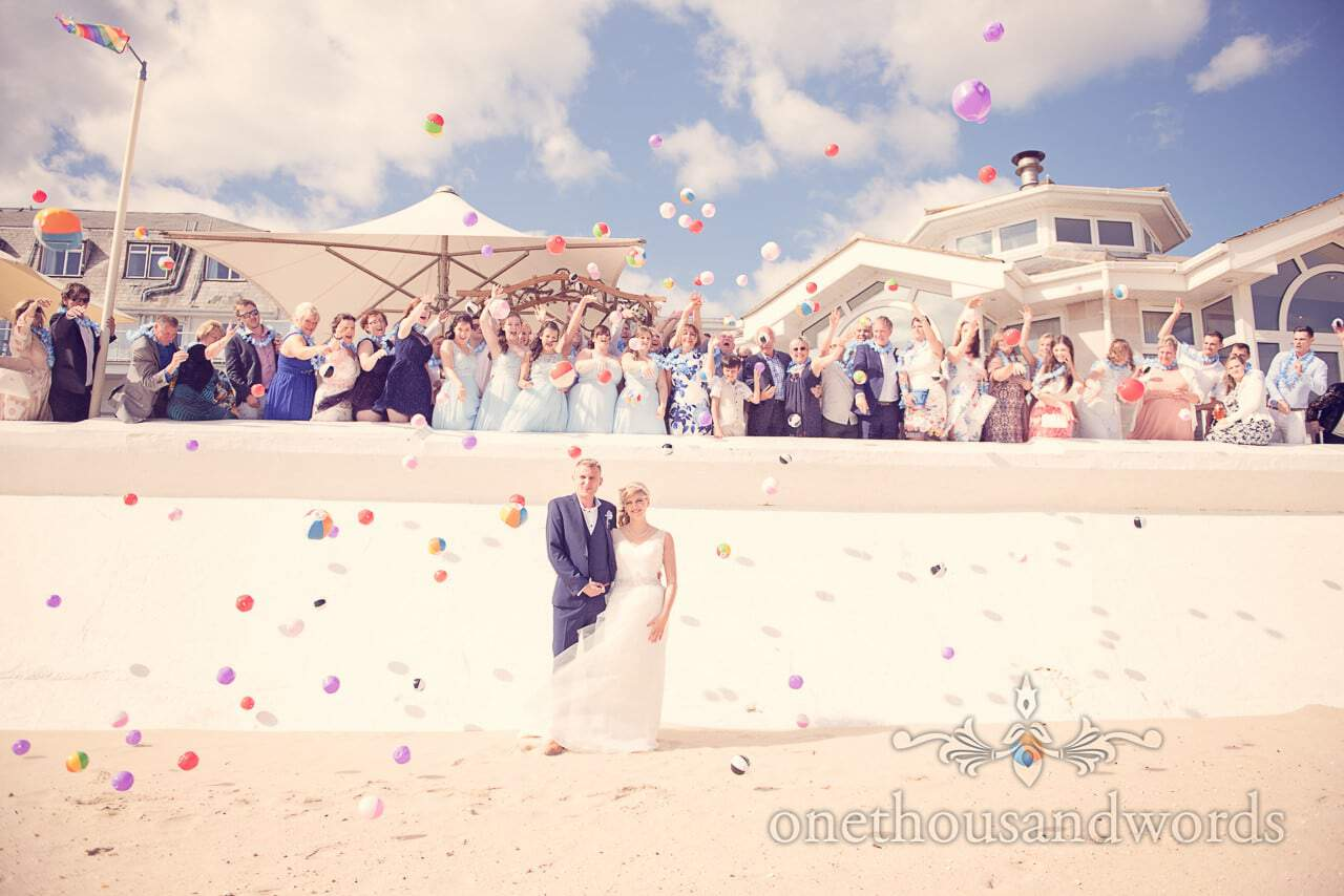 Bride and groom with beach ball wedding confetti at Sandbanks Hotel