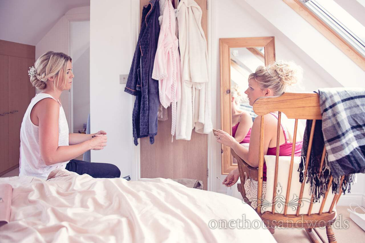 Bride and maid of honour talk about wedding makeup in brides bedroom