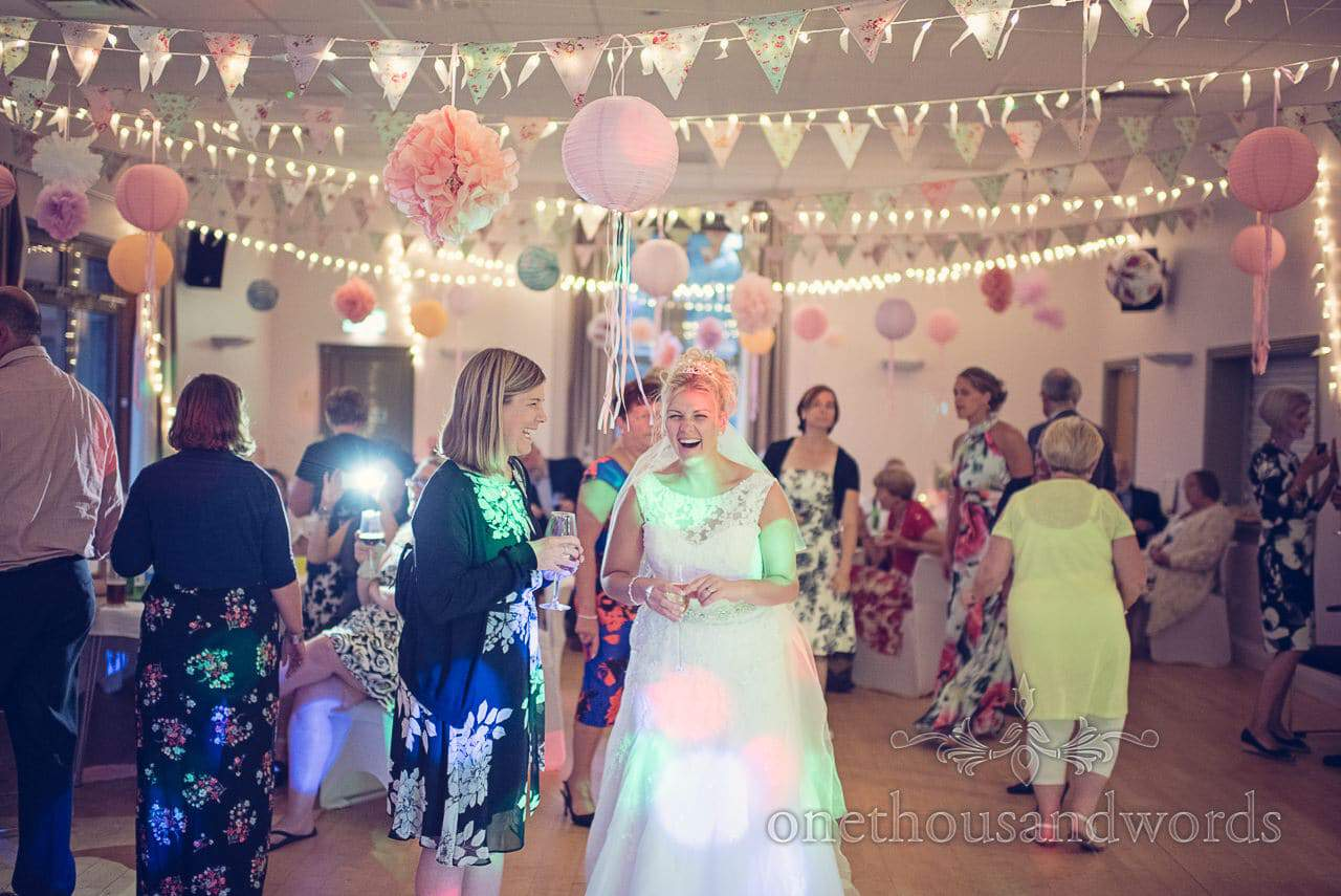 Bride and wedding guest laughing under fairy lights, bunting and chinese lanterns