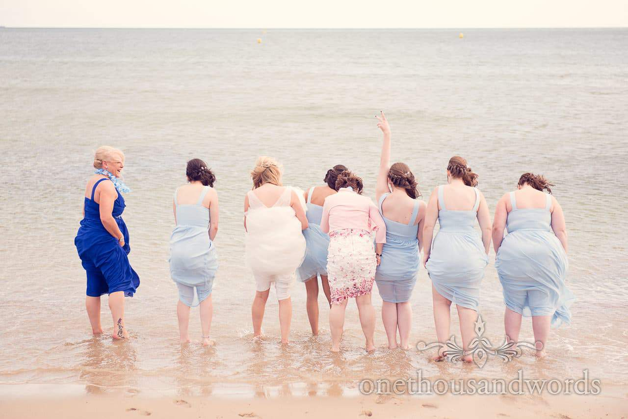 Bride, bridesmaids and mother of the bride take a dip in the sea at beach wedding
