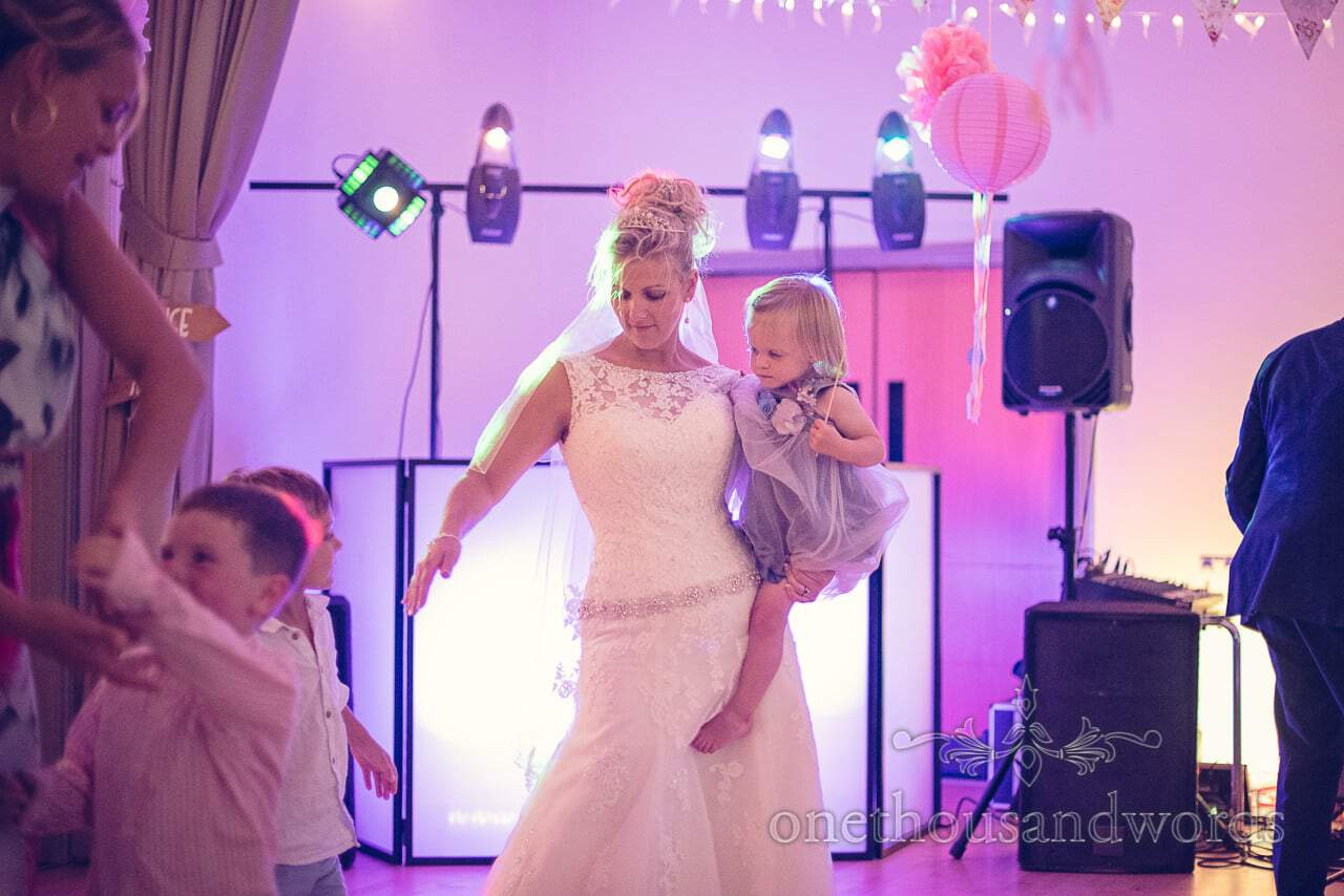 Bride dances with flowergirl at wedding disco in Harmans Cross Village Hall wedding venue