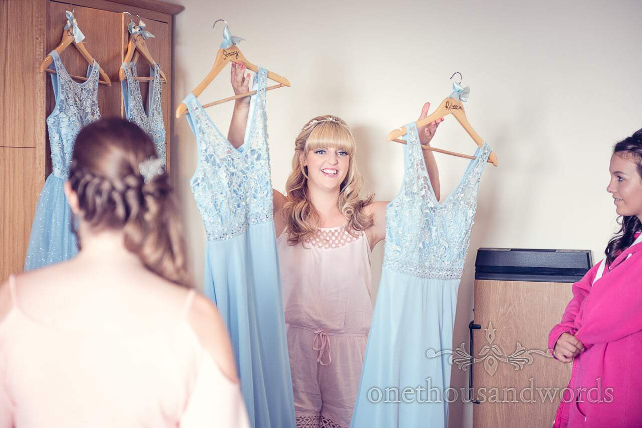 Bride hands out light blue detailed bridesmaids dresses on wedding morning