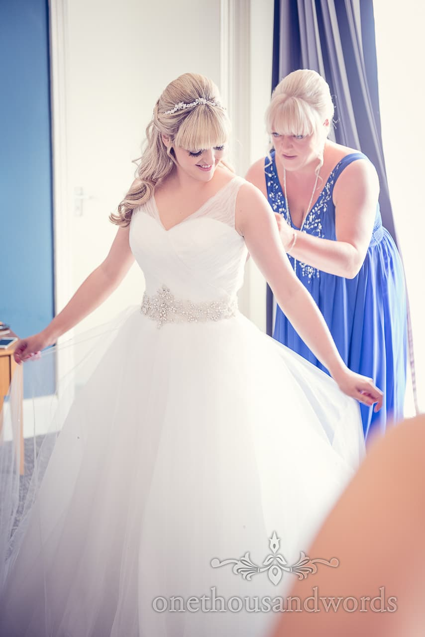 Bride helped into her wedding dress by her mother on wedding morning photograph