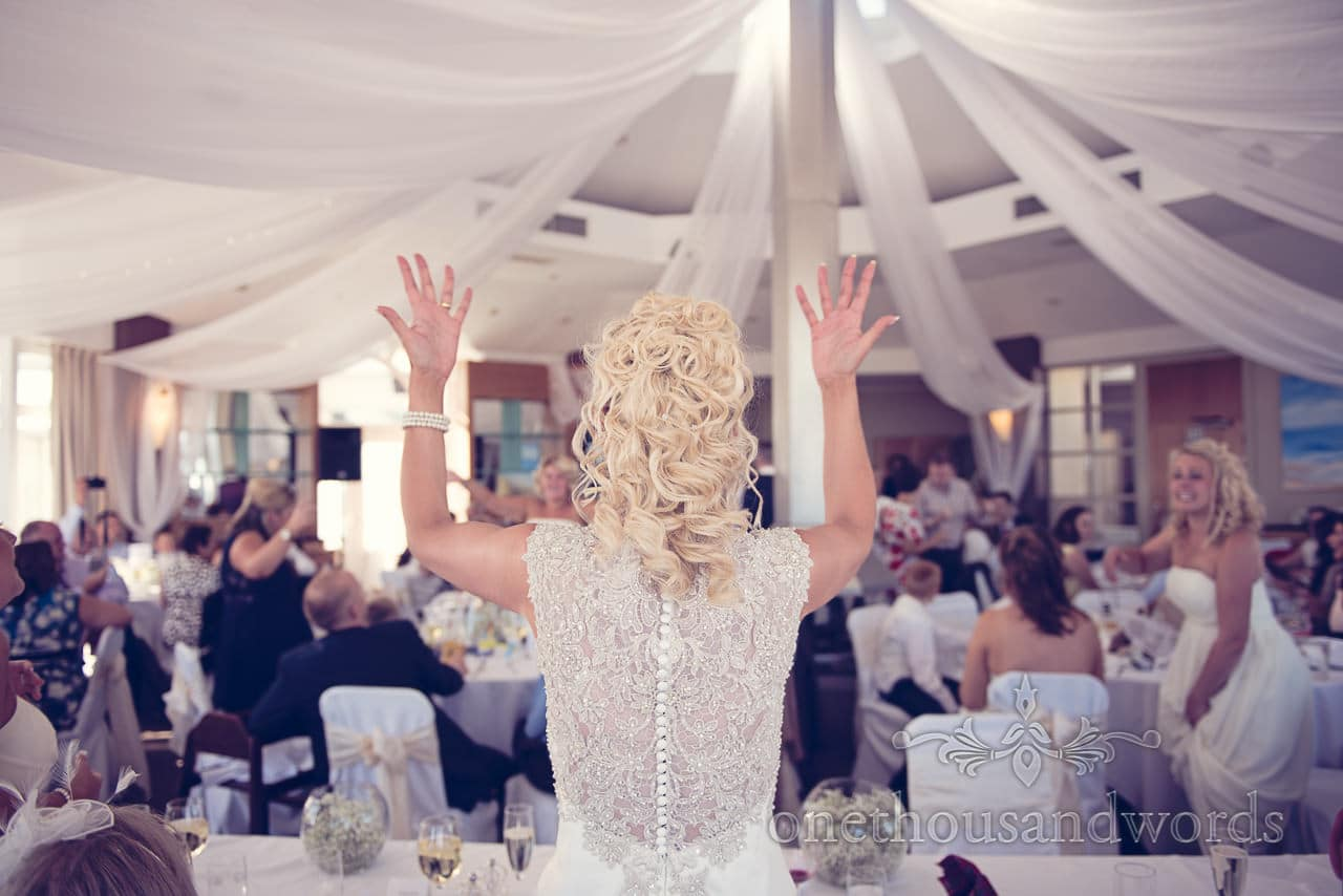 Bride in detailed diamate wedding dress dances at her wedding guests at Sandbanks Hotel Wedding