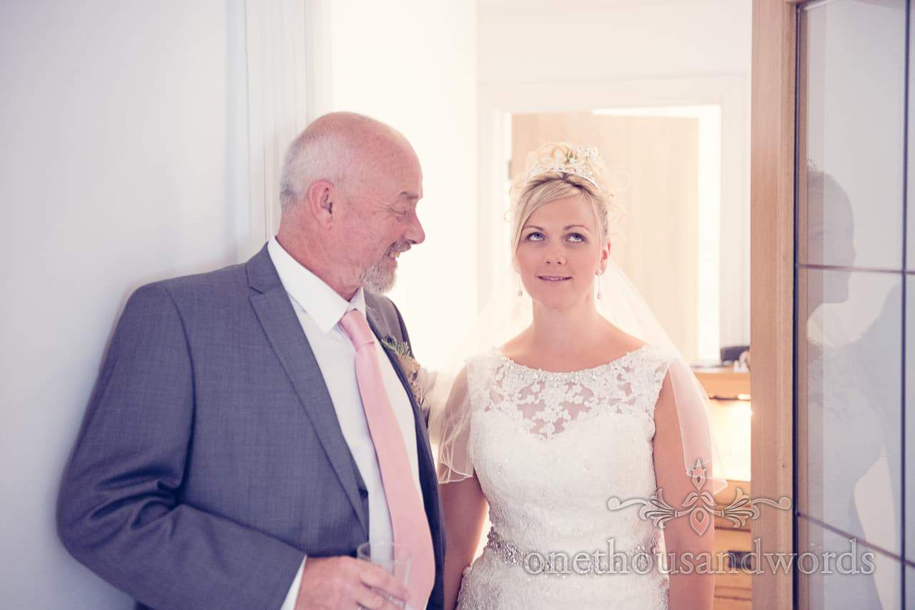 Bride in detailed white wedding dress and tiara rolls eyes at father of the bride's joke