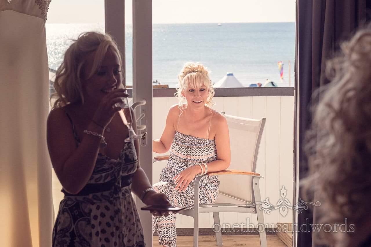 Bride sits on balcony at Sandbanks Hotel Wedding