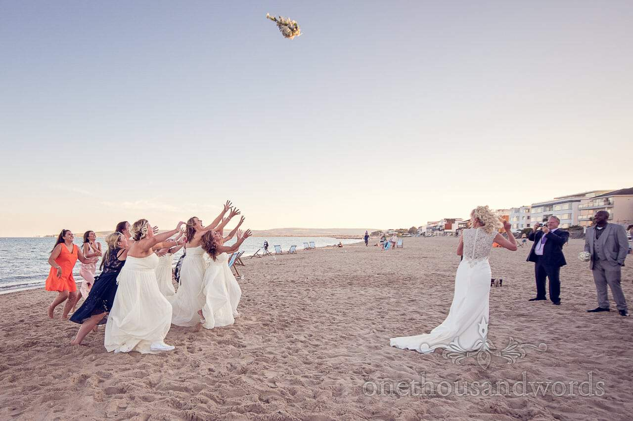 Bride throws wedding bouquet on sandbanks beach in Dorset