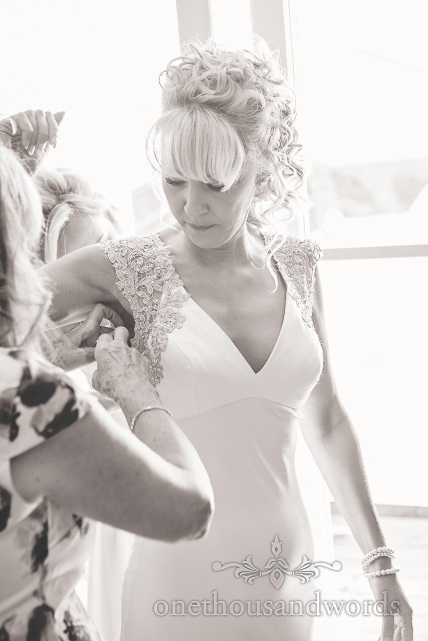 Brides dress is adjusted on morning of Sandbanks Hotel Wedding