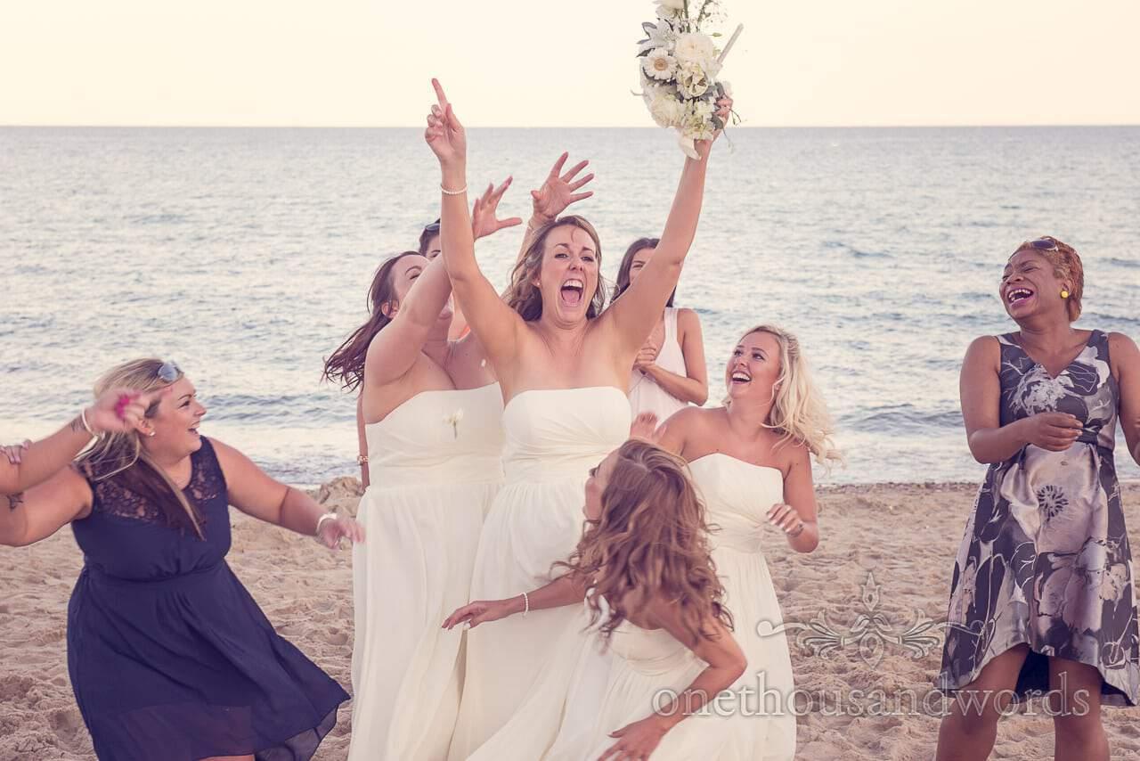 Bridesmaid catches the wedding bouquet on Sandbanks beach, Poole