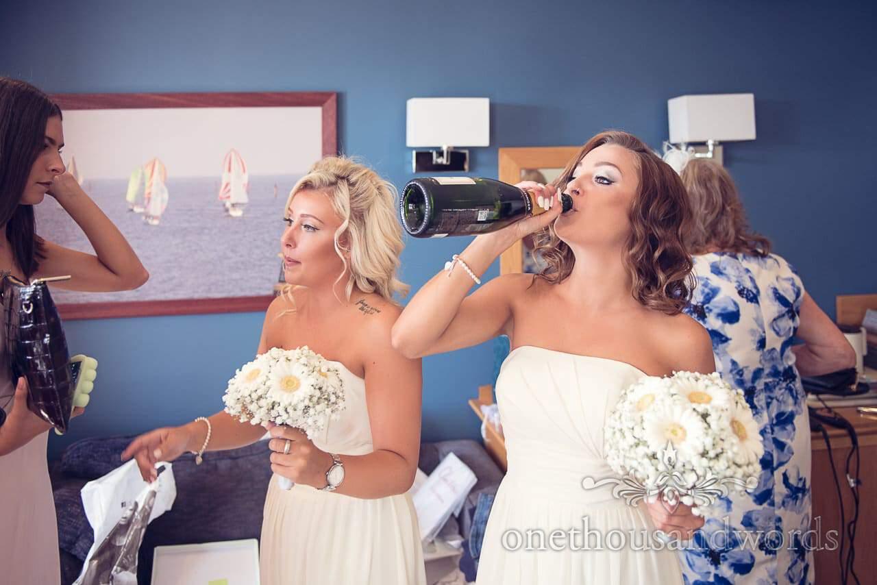 Bridesmaid has a little drink at Sandbanks Hotel Wedding