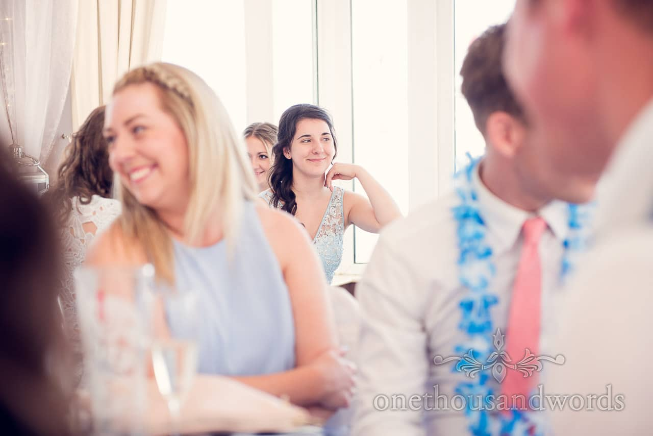Bridesmaid in light blue bridesmaids dress smiles during wedding speeches