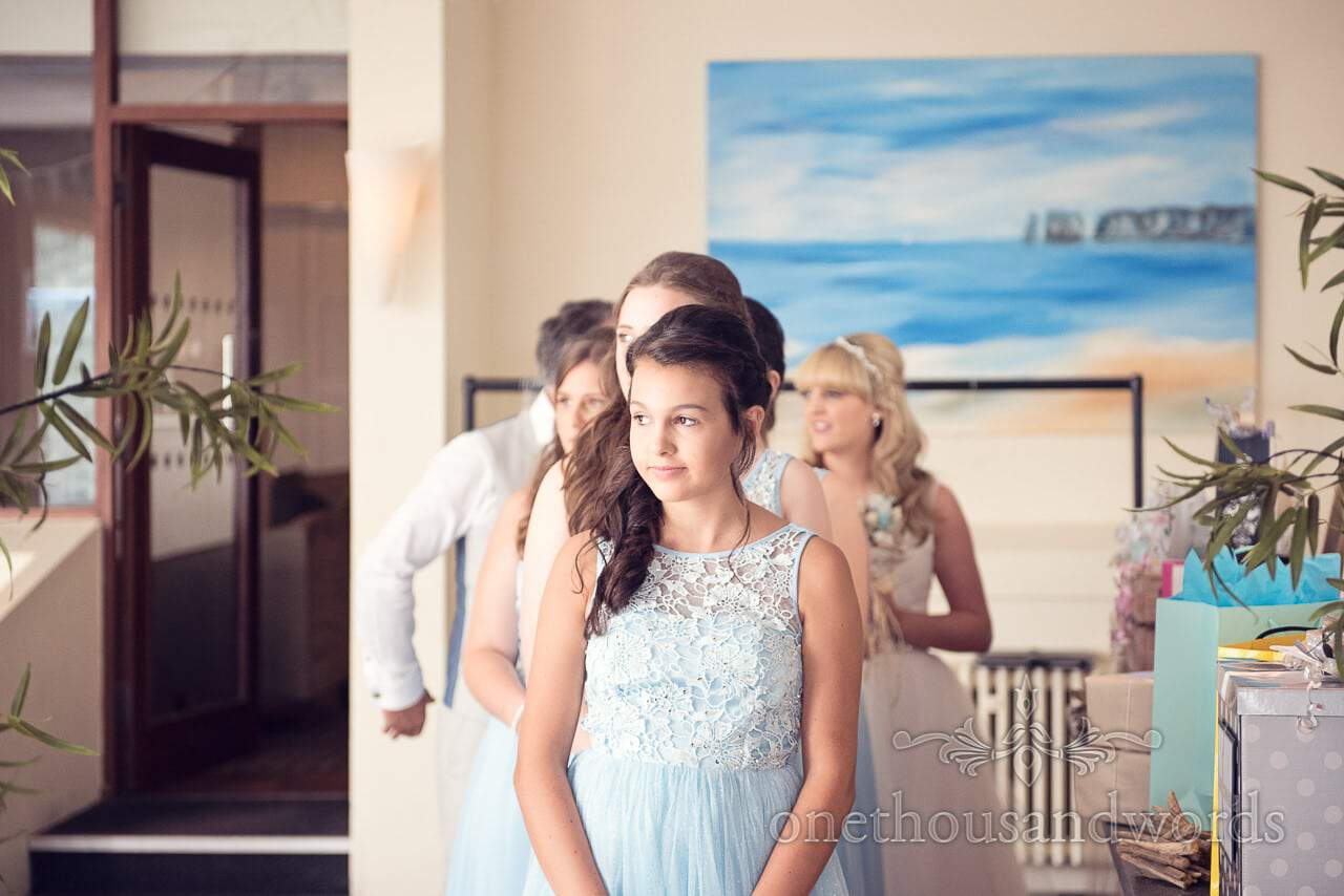 Bridesmaid in light blue dress waits to lead in wedding procession