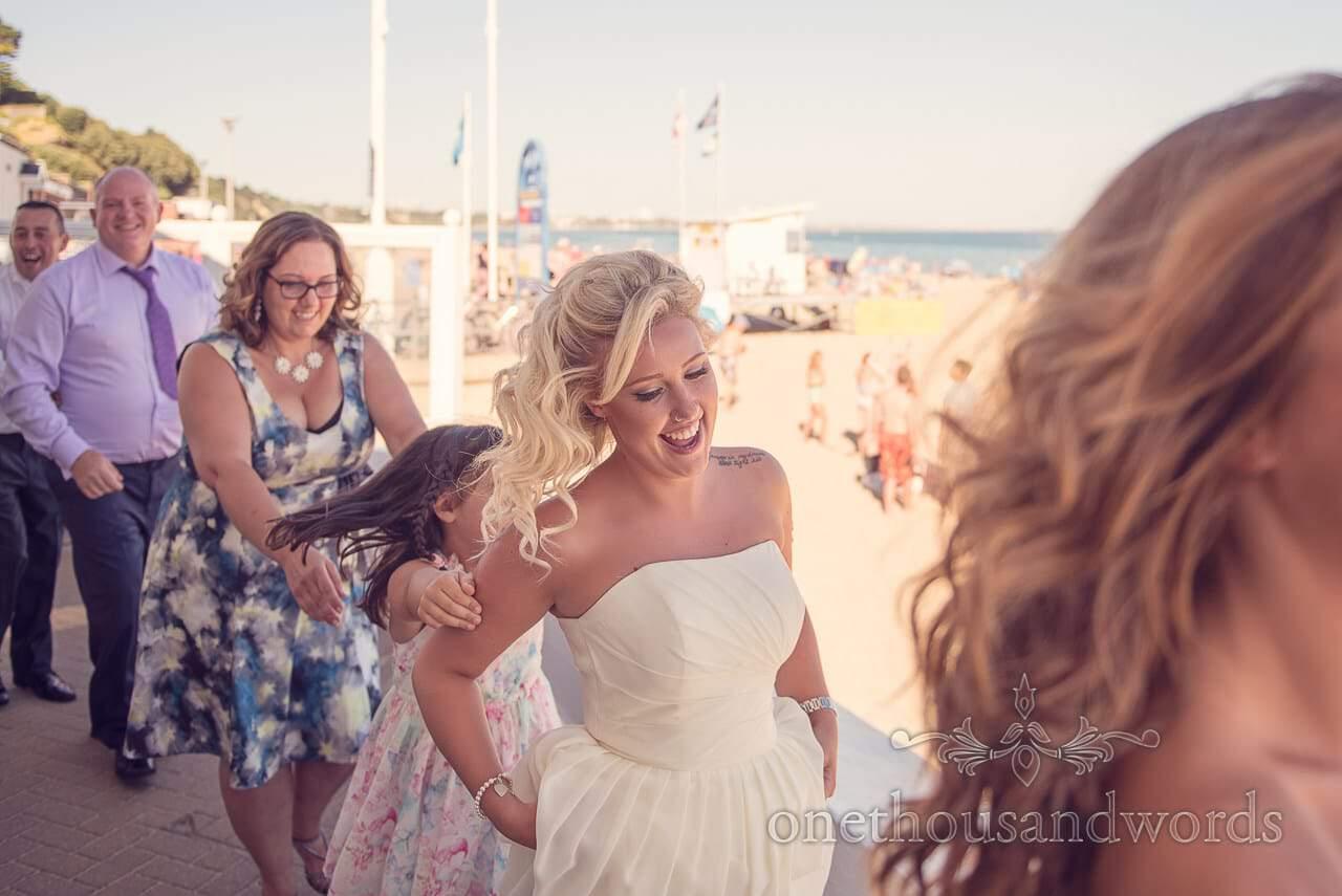 Bridesmaid in yellow dances past Sandbanks beach at Sandbanks Hotel Wedding