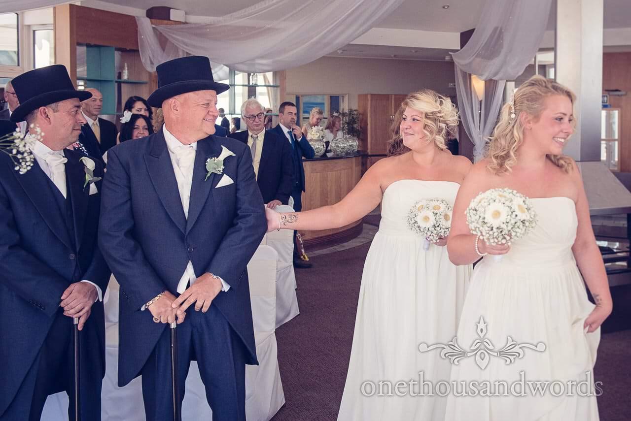 Bridesmaid reaches out to groom at Sandbanks Hotel Wedding