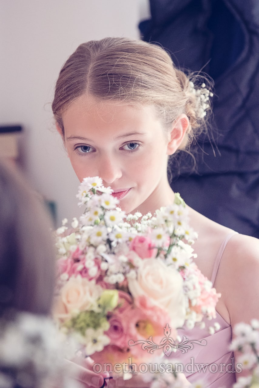 Bridesmaid smells pastel countryside flowers bouquet on wedding morning