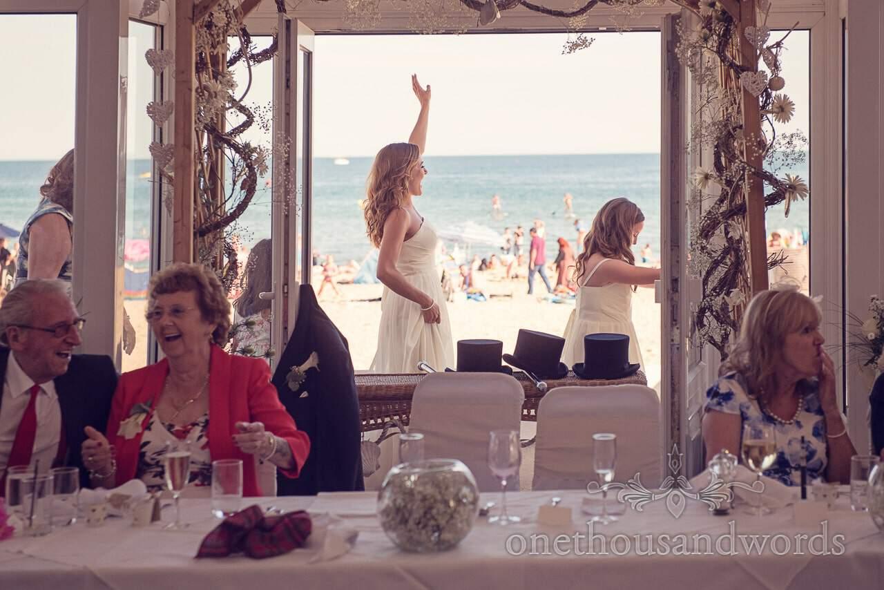 Bridesmaids dance past Sandbanks beach in conga line at Sandbanks Hotel Wedding